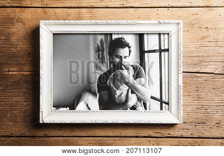 Picture frame with black and white picture of young father at home holding his cute baby daughter. Fathers day concept. Studio shot on wooden background.