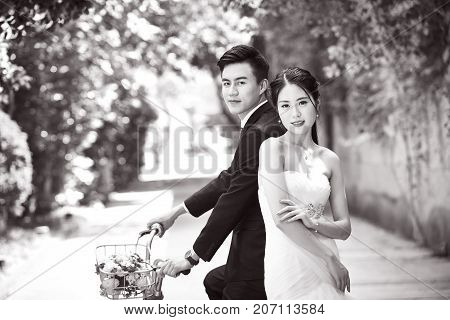 newly-wed asian bride and groom taking picture with a bicycle black and white.