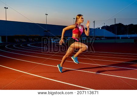 Runner sprinting towards success on run path running athletic track. Goal achievement concept. Female athlete sprinter doing a fast sprint for competition on red lane at an outdoor field stadium.