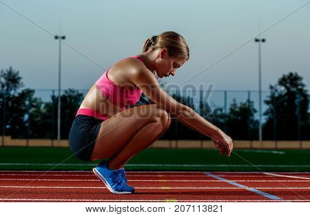 Picture of beautiful young European female runner or sprinter sitting on outdoor stadium track, feeling exhausted after sprint or marathon. Jogging, sport, healthy active lifestyle concept.