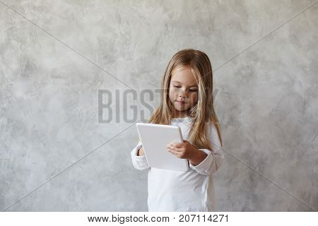 Adorable sweet female kid posing isolated at grey concrete wall dressed in casual white shirt surfing internet watching pictures and videos online or playing video games using digital tablet