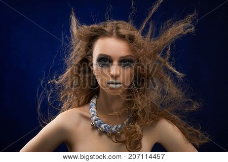 Portrait of a pretty girl with mysterios make-up. She has curly dispersing hair and a bijou on her neck. The photo was taken in the studio with a dark background.