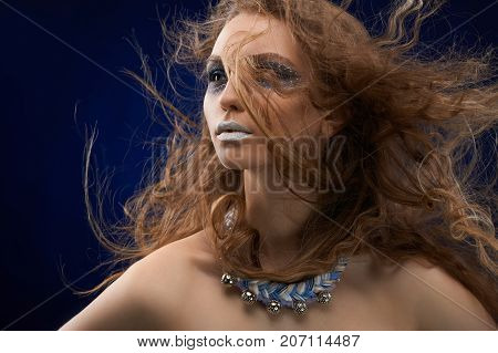 A photo of a beatiful girl with curly, long, dispersing hair and mysterios make-up. She has white lips and pattarns on her face. There is a bijou on her neck. Model s skin is very healthy and smooth.