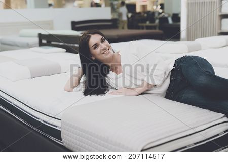 A Woman Chooses A Mattress In A Store. She Decided To Lie Down And Try It