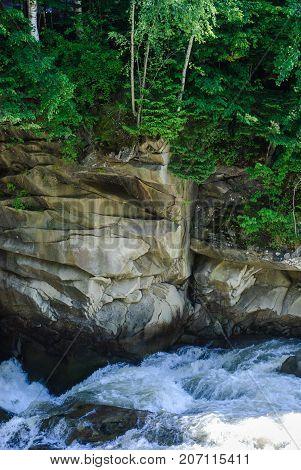 Stormy stream of a mountain river. Stone precipice. Rocky coast