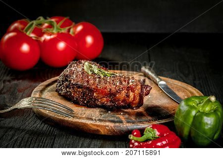 Grilled steak seasoned with spices and fresh herbs served on a wooden board with fresh tomato and red and green peppers. Black wooden background. Still life