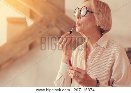 Brighten your day. Waist up of a nice aged stylish woman using her lip gloss while doing her make up at home