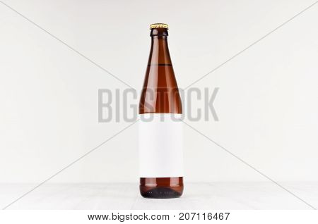 Brown NRW beer bottle 500ml with blank white label on white wooden board mock up. Template for advertising design branding identity.
