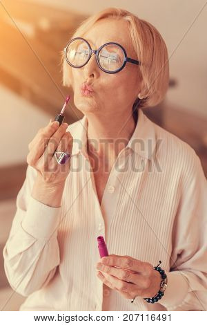 One hundred kisses. Portrait of a nice aged beautiful woman using her lip gloss at home while doign her make up
