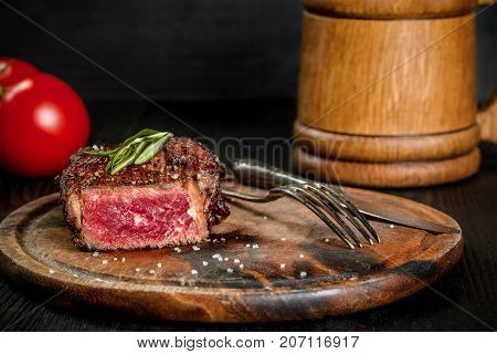 Grilled steak seasoned with spices and fresh herbs served on a wooden board with wooden mug of beer and fresh tomato. Black wooden background. Still life