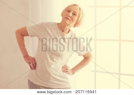Lean right. Nice sporty aged woman doing leaning exercises and enjoying sport activities while taking care of your health.