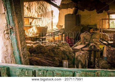 Sunlight floods into a derelict barn full of antiques