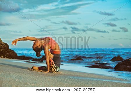Meditation on sunset sky background. Young active woman sit in yoga pose on sand beach stretching to keep fit and health. Healthy lifestyle outdoor fitness sports activity on summer family holiday.