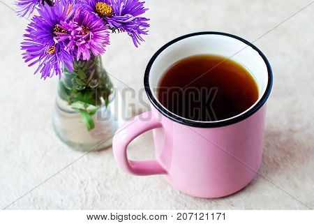 A pink mug of black tea with bergamot on a light background and purple flowers in a glass vial.