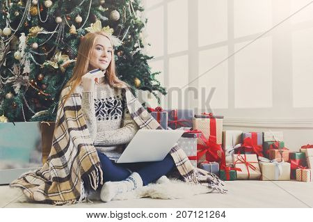 Young woman with credit card shopping online on laptop in christmas interior. Girl sitting under decorated fir tree among lots of wrapped presents. Preparing to xmas, bying on winter sales. Copy space