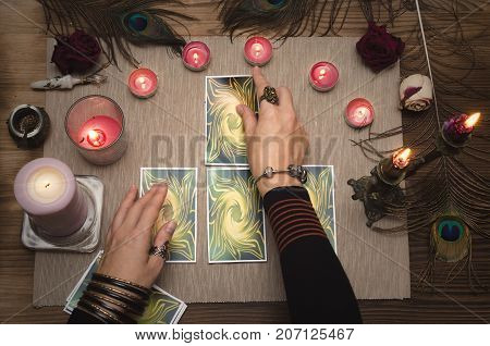 Tarot cards on the paranormal table and fortune teller female hands. Reading future.