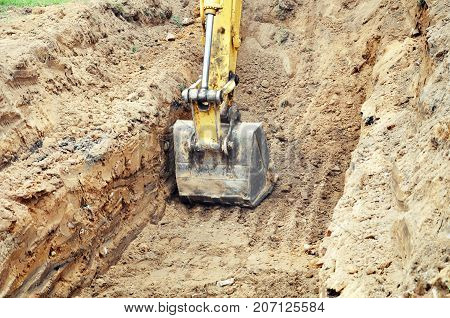 Excavator bucket with in the sandy trench in work.