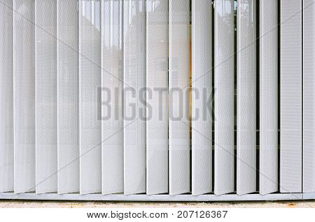 White modern structure of metal perforated vertical panels.