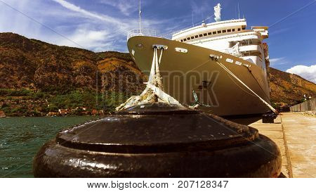 The Cruise Liner Is Moored At The Pier In The Port In A Bay Surrounded By Mountains