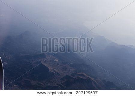 Mountain peaks in mornin fog during airplane flight