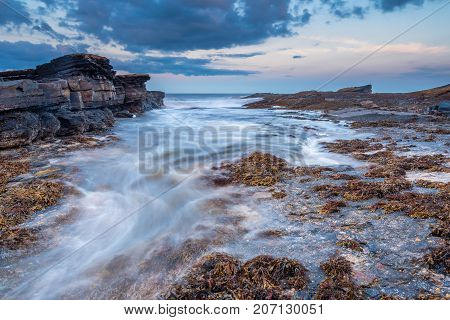 Surging Tide on Howick Coastline, at the rocky shoreline at Howick on the Northumberland coasts AONB, showing motion blur of the North Sea