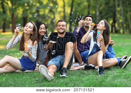 Five Friends Women And Men Inflate Soap Bubble Outdoors