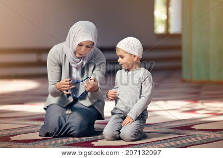 Muslim mother teach her son praying inside the mosque.