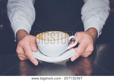 Close up of barista holding a cup of fresh and hot latte macchiato coffee