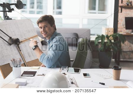 Positive mood. Portrait of delightful young engineer is sitting near drawing board and holding pencil while looking at camera with joy. He is working in cozy office. Copy space in the right side