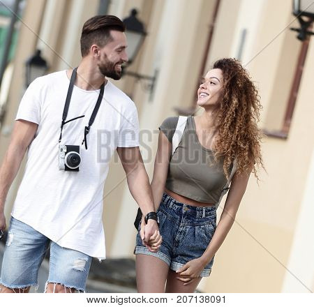A loving couple of tourists look at each other and  walking