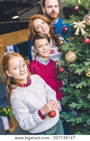 young happy family decorating christmas tree and looking at camera