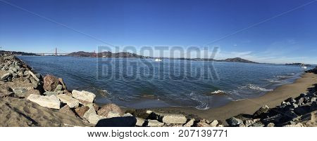 A pano shot of the beach in the bay with the GGB in background