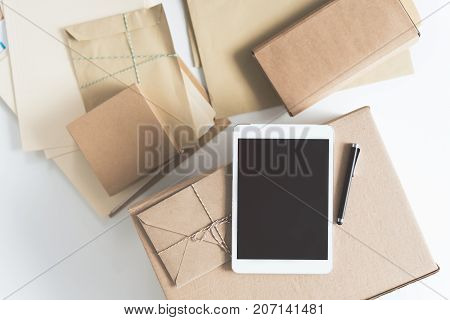 Digital panel. Close-up top view of smart tablet with boxes and envelopes are on table in sorting center. Copy space in the left side