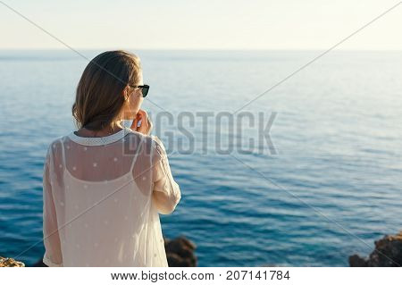 Young beautiful lonely girl on the beach looking into the distance of the sea at sunset