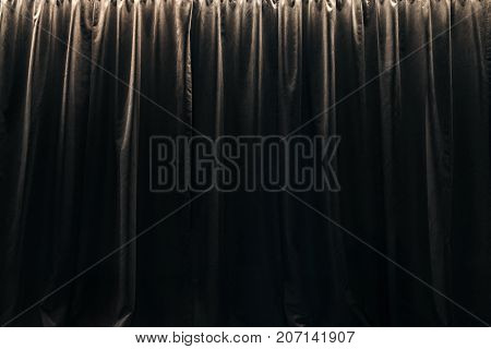 Closed curtain of black velvet curtains. Part of the interior
