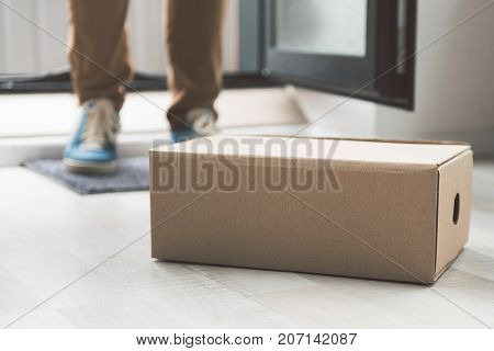 Close up cardboard package locating on floor. Male legs situating near it. Copy space