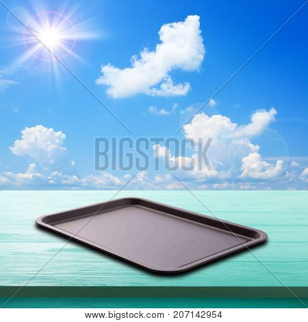 Empty baking tray for pizza on wooden desk of free space and spring time. Blue sky with beautiful clouds and bright sun on a summer day as a background. Mock up for design.