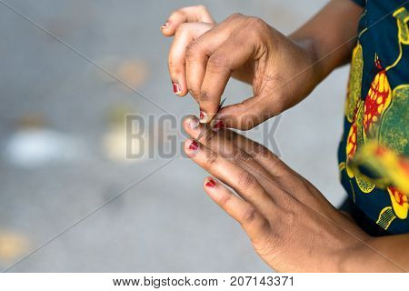 Young African Woman Doing Her Nails Outdoors