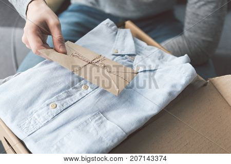 Focus on close up man hand holding seal envelope near new shirt in carton box