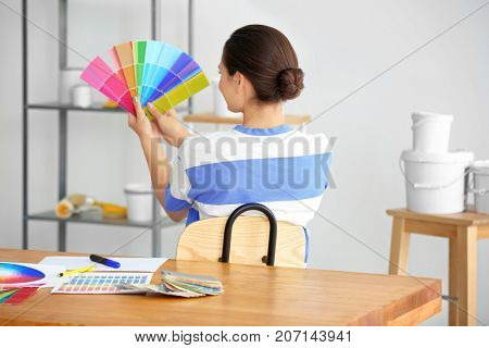Female decorator holding color palette samples in office