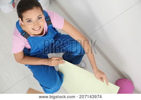Young female decorator with different wallpaper samples in room