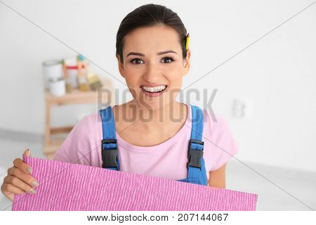 Female decorator holding color wallpaper indoors