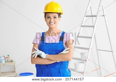Young female decorator near ladder indoors