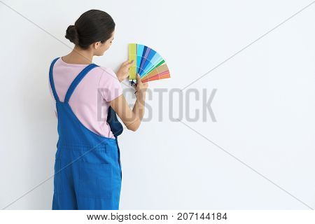 Female decorator holding color palette samples on white background