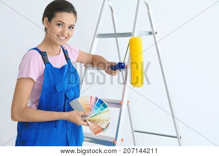 Young female decorator with paint roller and color palette samples near ladder on white background