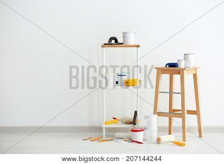 Composition with decorator's tools near white wall