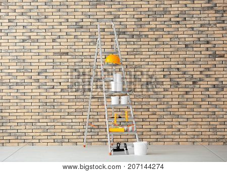Composition with decorator's tools and paint on ladder near brick wall