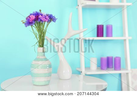 Lilac accent in modern interior. Table with beautiful cornflowers in living room