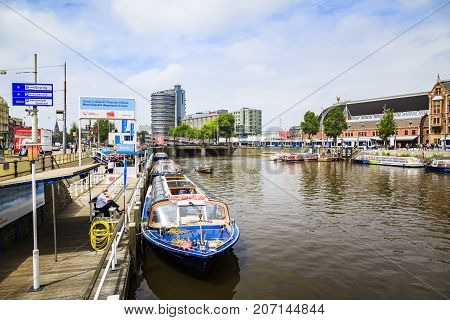 AMSTERDAM NETHERLANDS - JUNE 21 2016: One of Amsterdam's canal next to Amsterdam Centraal in a cloudy day. Amsterdam Netherlands.