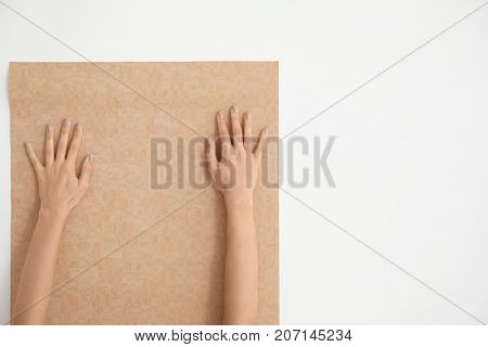 Female decorator gluing color wallpaper on white background